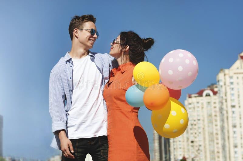 Счастливые человек и женщина с воздушными шарами на улице города стоковое фото rf