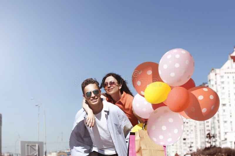 Счастливые человек и женщина с покупками и воздушными шарами стоковое фото
