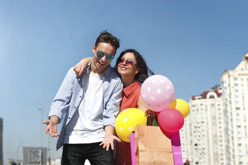 Счастливые человек и женщина с покупками и воздушными шарами стоковая фотография