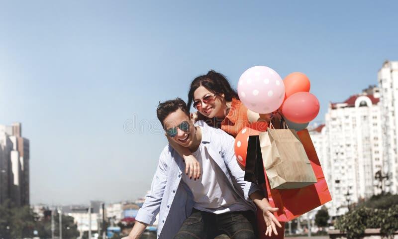 Счастливые человек и женщина с покупками и воздушными шарами стоковые фото