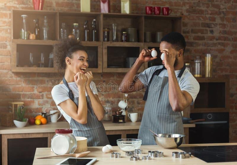 Счастливые черные выпечка пар и потеха иметь в кухне стоковое фото