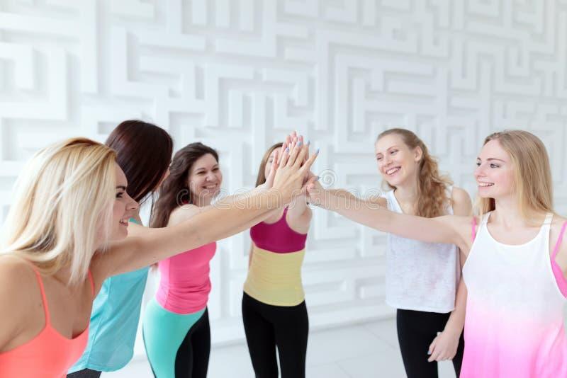 Счастливые sporty женщины нося руки sportswear присоединяясь стоковое фото rf