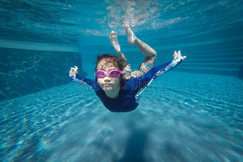 Счастливый азиатские заплыв девушки и пикирование подводные, семейный отдых лета с ребенком, ослабляют, развлечения стоковые фото