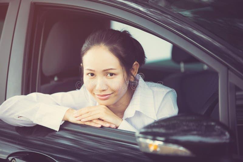 Счастливый азиатский водитель женщины сидя внутри ее автомобиля стоковые изображения rf