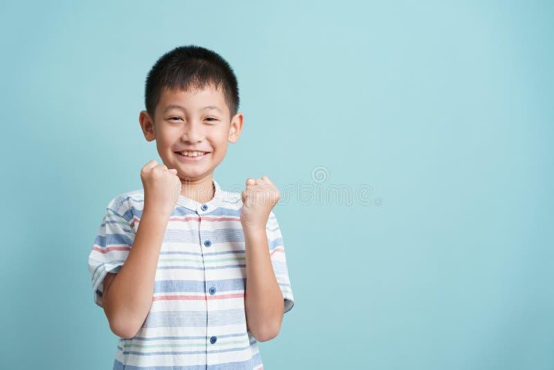 Счастливый азиатский мальчик, стоящий на синем фоне изолирован, Портрет милого человека успех счастье и улыбка стоковые изображения rf
