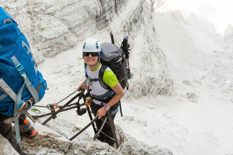 Счастливый альпинист достигая саммит лестницы стоковое изображение rf