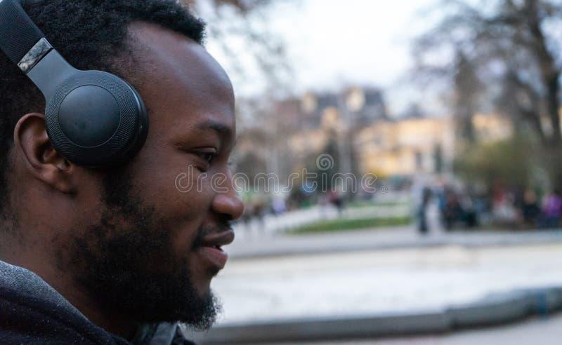 Счастливый африканский молодой парень с бородой и наушники в парке стоковые изображения