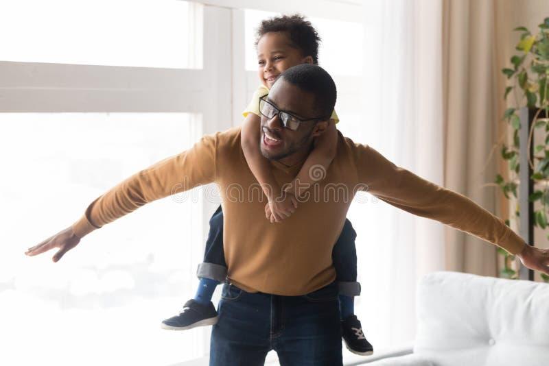 Счастливый африканский отец перевозя по железной дороге меньшего сына играя совместно дома стоковая фотография rf