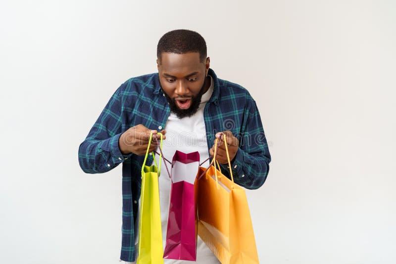 Счастливый Афро-американский человек держа хозяйственные сумки на белой предпосылке Концепция праздников стоковое изображение