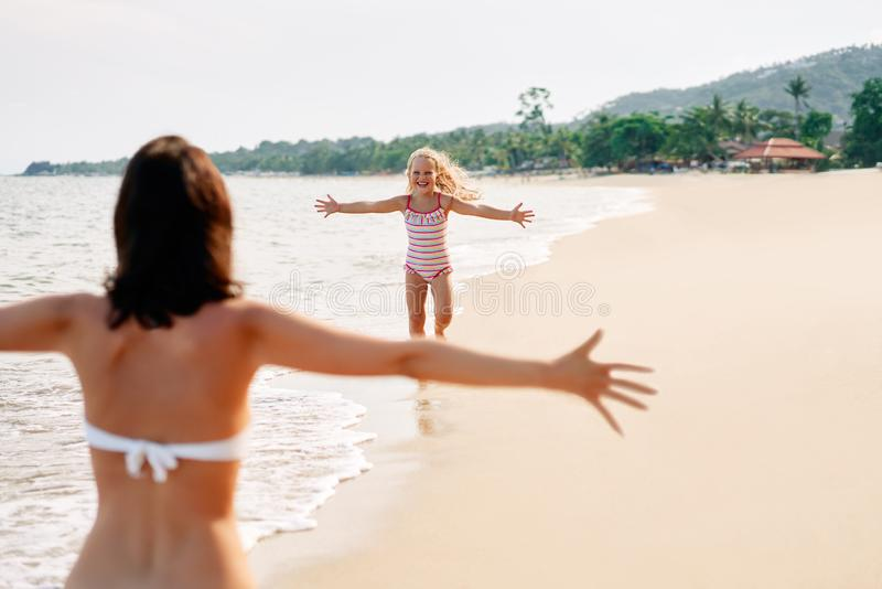 Счастливый бег маленькой девочки к ее матери для объятий на тропическом пляже стоковое фото rf