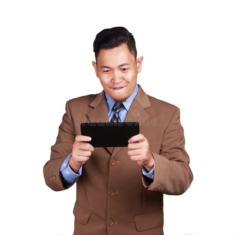 Счастливый бизнесмен играя на его таблетке стоковое изображение rf