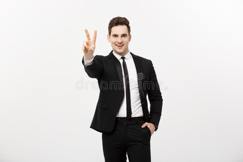 Счастливый бизнесмен показывая 2 пальцы или жеста победы, против серой предпосылки Успех в деле, работе и стоковые фотографии rf