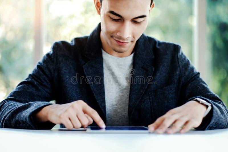 Счастливый бизнесмен работая на планшете цифров в офисе Сидеть на столе и усмехаться стоковые изображения