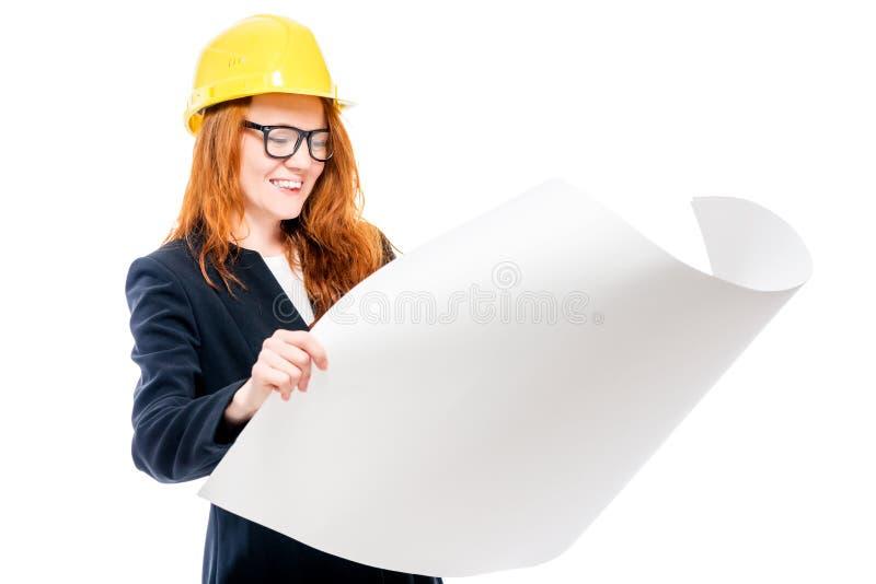 счастливый босс женщины в желтой трудной шляпе с чертежами стоковое изображение