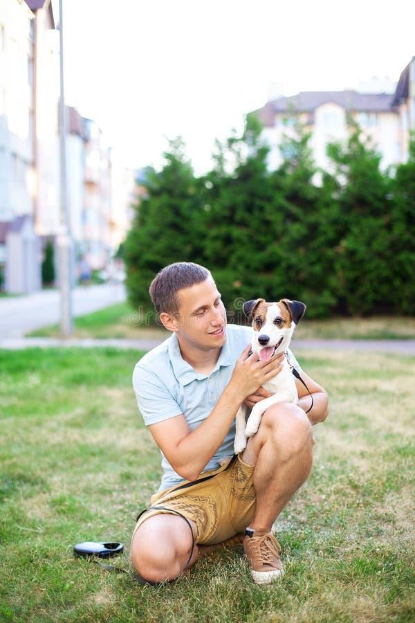 Счастливый владелец идет с прелестными собакой и объятием Джек Рассела в растительности парка Концепция приятельства между huma стоковая фотография
