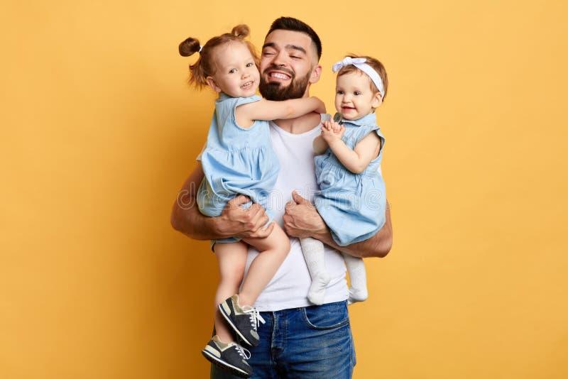 Счастливый внушительный папа держа его любимых дочерей в руках стоковое фото