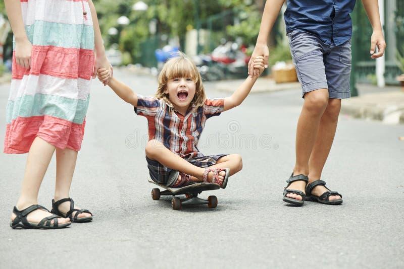 Счастливый возбужденный ребенк на скейтборде стоковая фотография rf