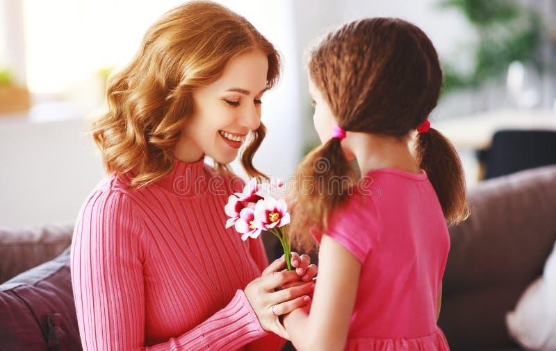 Счастливый День матери! дочь ребенка дает матери букет цветков тюльпанам и открытке стоковое фото rf