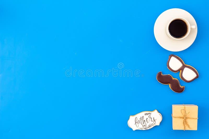 Счастливый день отца со стеклами, печеньями усика, подарком и кофе на голубом модель-макете взгляда сверху предпосылки стоковая фотография rf