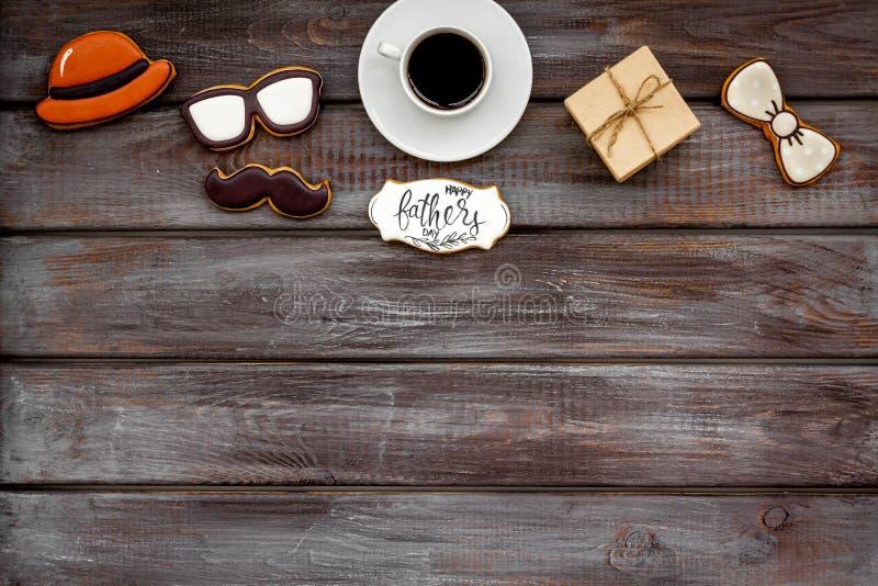 Счастливый день отца со шляпой, стеклами, печеньями усика, подарком и кофе на деревянном модель-макете взгляда сверху предпосылки стоковое фото rf
