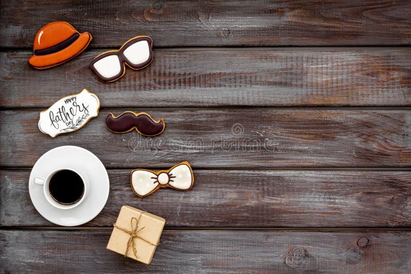 Счастливый день отца со шляпой, стеклами, печеньями усика, подарком и кофе на деревянном модель-макете взгляда сверху предпосылки стоковые фото
