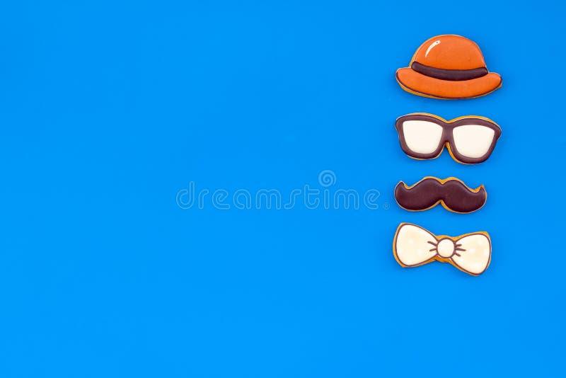 Счастливый день отца с бабочкой, усиком, стеклами и печеньями шляпы на голубом модель-макете взгляда сверху предпосылки стоковое фото rf