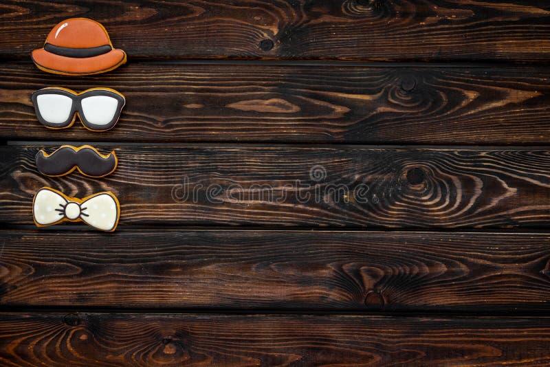 Счастливый день отца с бабочкой, усиком, стеклами и печеньями шляпы на деревянном модель-макете взгляда сверху предпосылки стоковые изображения rf
