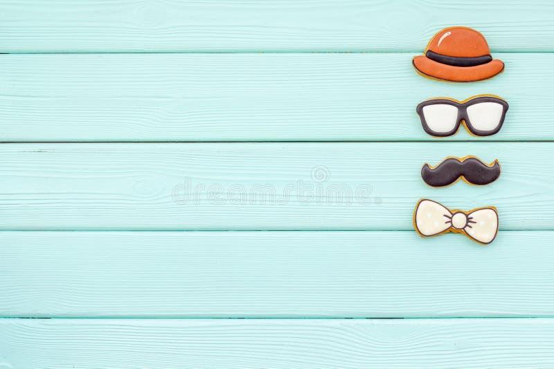 Счастливый день отца с бабочкой, усиком, стеклами и печеньями шляпы на модель-макете взгляда сверху предпосылки мяты зеленом дере стоковое изображение