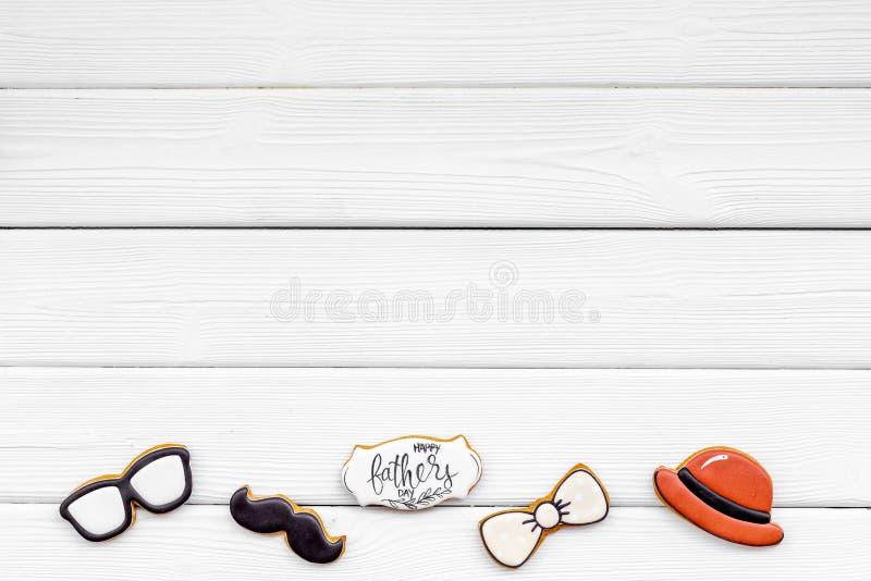 Счастливый день отца с бабочкой, усиком, стеклами и печеньями шляпы на белом модель-макете взгляда сверху предпосылки стоковое изображение rf