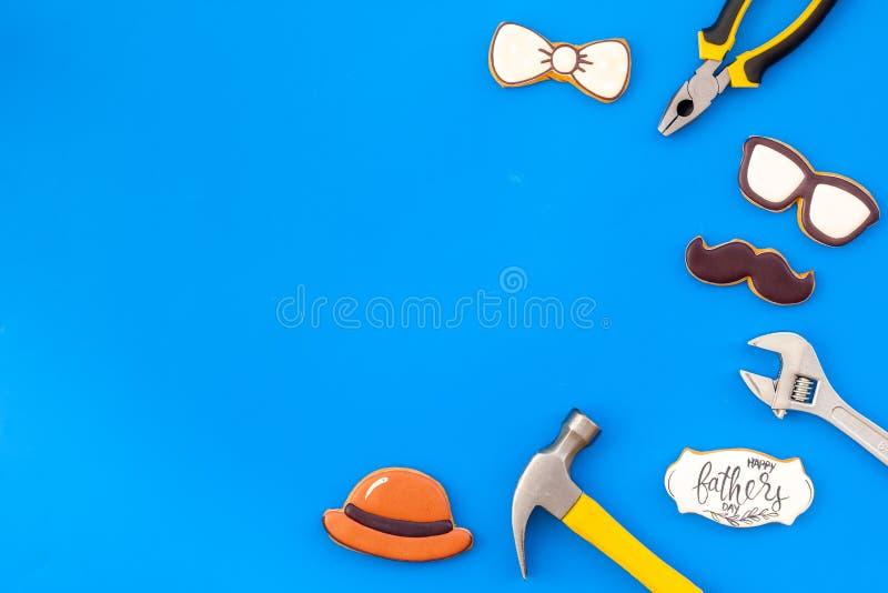 Счастливый день отца с бабочкой, усиком, стеклами и печеньями и аппаратурами шляпы на голубом модель-макете взгляда сверху предпо стоковые фотографии rf
