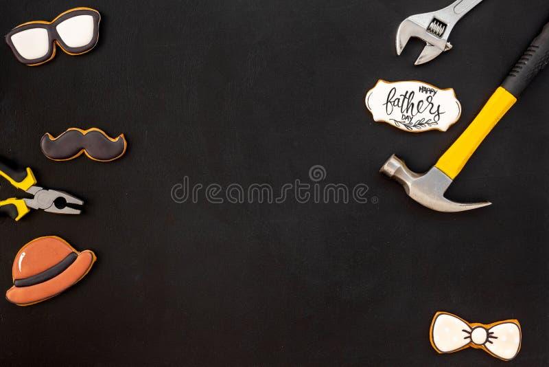 Счастливый день отца с бабочкой, усиком, стеклами и печеньями и аппаратурами шляпы на черном модель-макете взгляда сверху предпос стоковые изображения rf