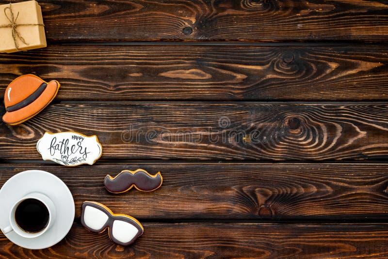 Счастливый день отца с усиком, стеклами и печеньями и аппаратурами шляпы на деревянном модель-макете взгляда сверху предпосылки стоковое изображение rf