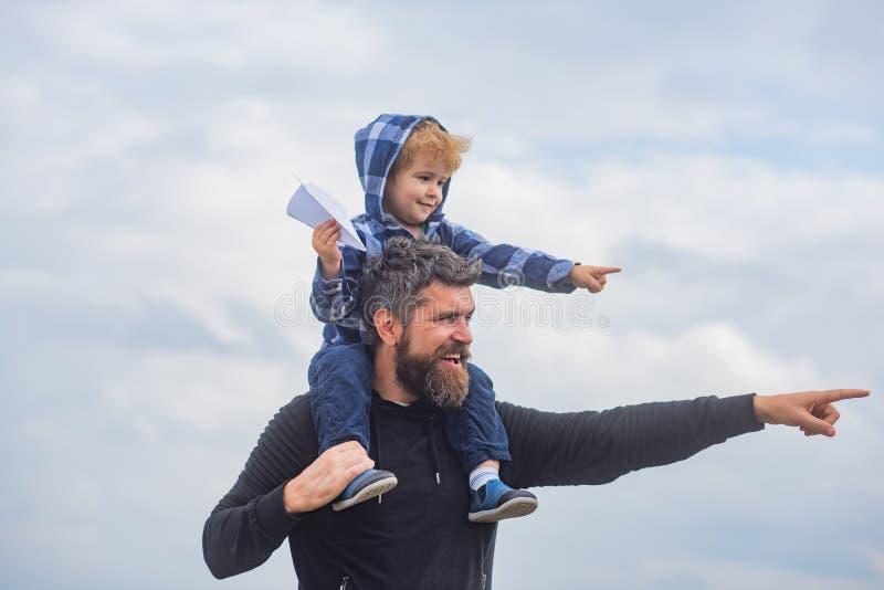 Счастливый день отцов Папа и сын играют на предпосылке неба Отец и сын строя совместно бумажный самолет стоковое изображение
