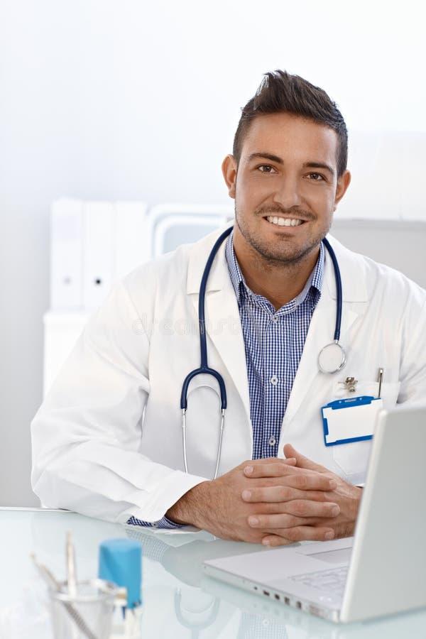 Счастливый доктор сидя на столе стоковые изображения