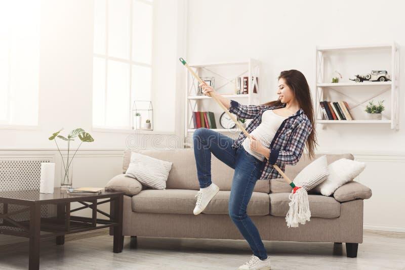 Счастливый дом чистки женщины с mop и потехой иметь стоковая фотография rf