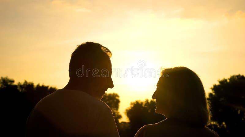 Счастливый достигший возраста супруг смотря один другого, романтичную дату на заходе солнца, нежные отношения стоковое изображение rf