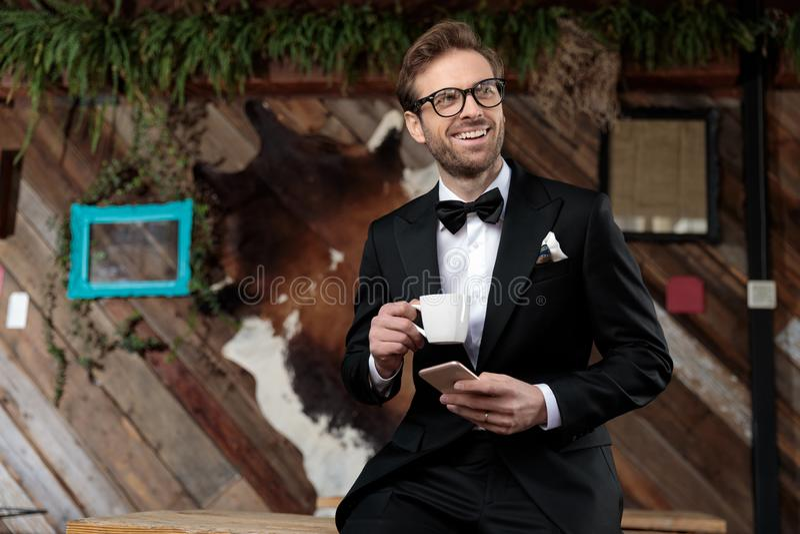 Счастливый жених, держащий чашку кофе и телефон стоковое изображение