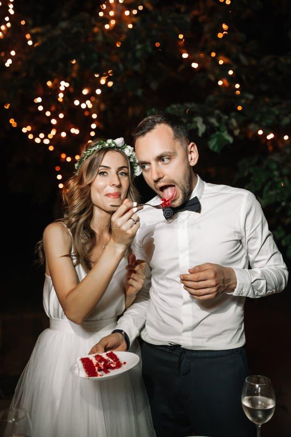Счастливый жених и невеста отрезал свадебный пирог в переднем украшении света гирлянды Выравниваться свадьбы внешний стоковая фотография