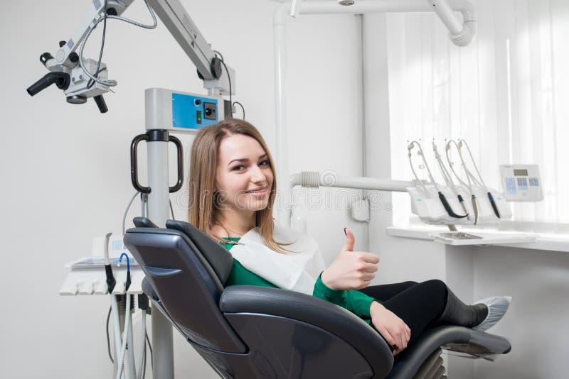 Счастливый женский пациент с расчалками на зубах сидя в зубоврачебном стуле, усмехаясь и показывая большие пальцы руки вверх посл стоковая фотография rf