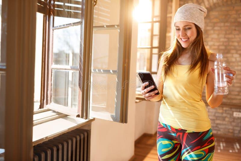 Счастливый женский смотреть на сотовом телефоне крытом стоковая фотография rf