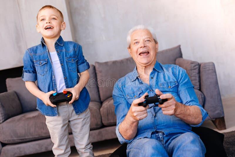 Счастливый жизнерадостный дед играя видеоигры стоковое фото