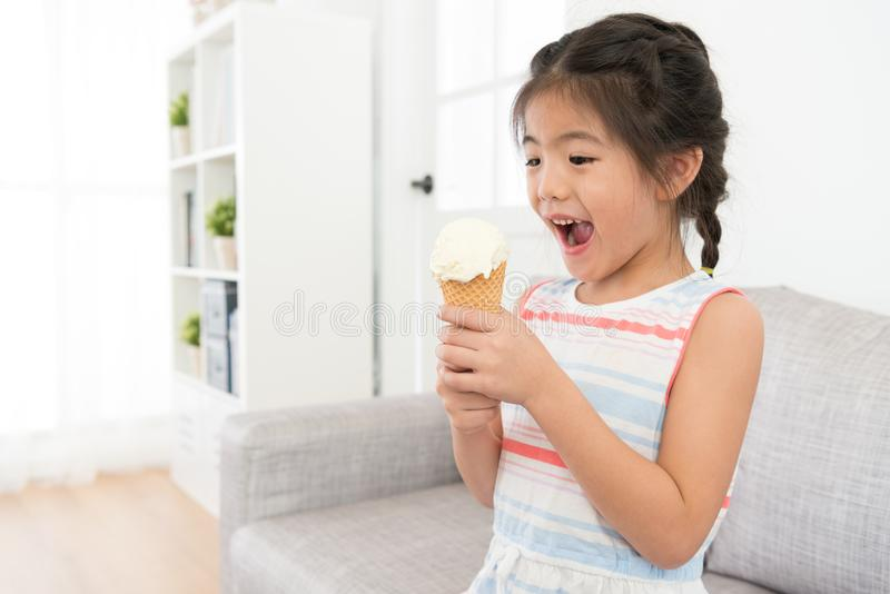 Счастливый жизнерадостный ребенк маленькой девочки держа мороженое стоковая фотография