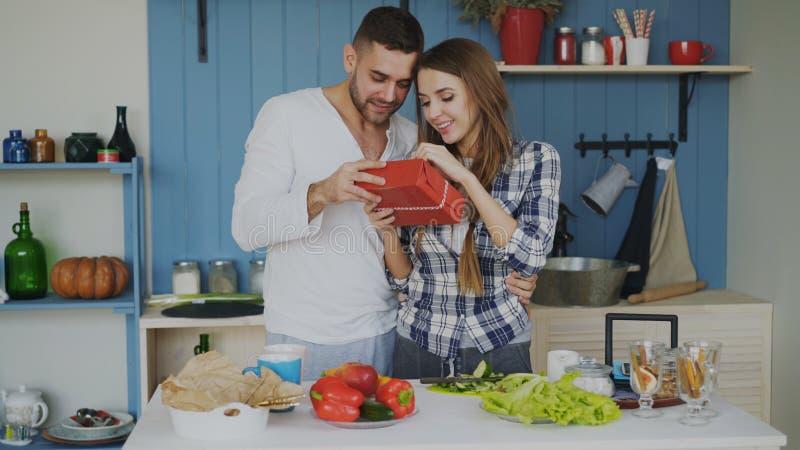Счастливый жизнерадостный человек удивительно его подруга с подарком дома в кухне пока она варя завтрак стоковое изображение rf