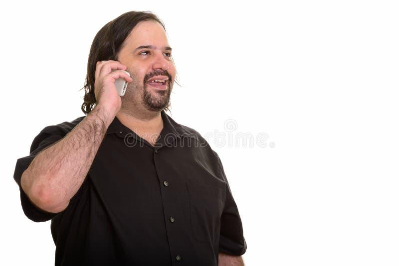 Счастливый жирный кавказский человек усмехаясь и смотря прочь пока говорящ o стоковое фото rf