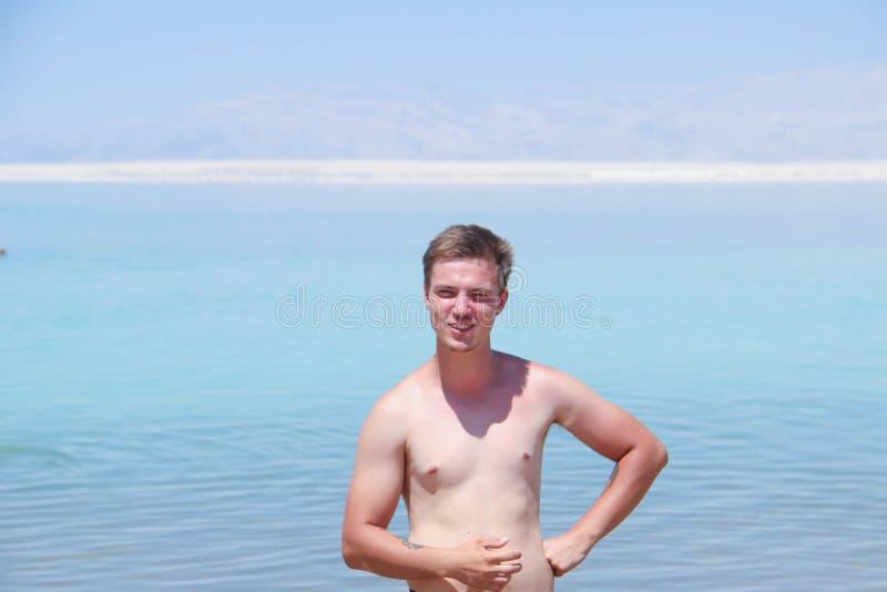 Счастливый задумчивый европейский человек с чуть-чуть торсом против голубого моря стоковые фотографии rf