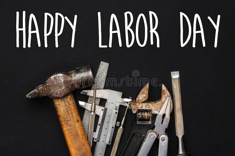 Счастливый знак текста Дня Трудаа Инструменты деятельности на черной предпосылке Se стоковые изображения