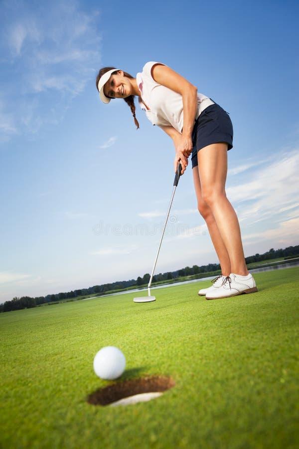 Счастливый игрок в гольф девушки кладя шарик в отверстие. стоковые фото