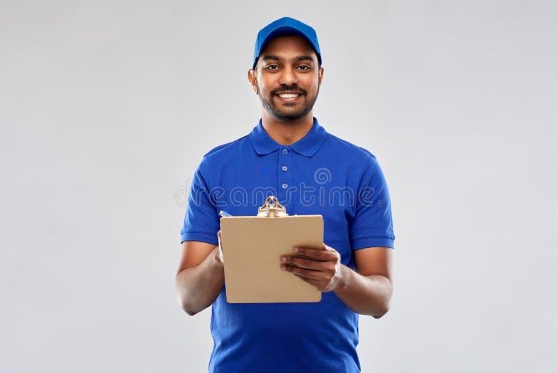 Счастливый индийский работник доставляющий покупки на дом с доской сзажимом для бумаги в сини стоковое фото