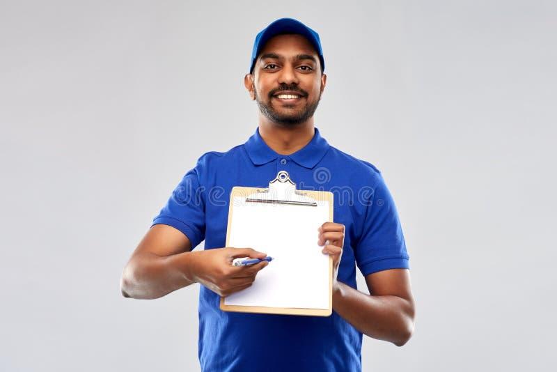 Счастливый индийский работник доставляющий покупки на дом с доской сзажимом для бумаги в сини стоковое фото rf