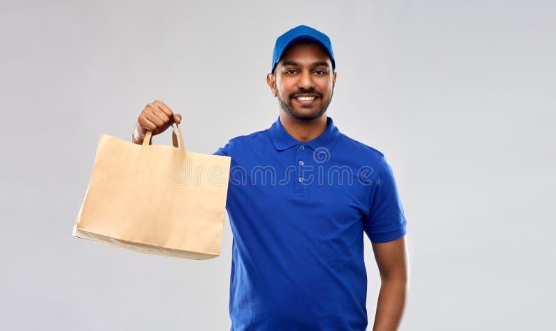 Счастливый индийский работник доставляющий покупки на дом с едой в бумажном мешке стоковые изображения rf